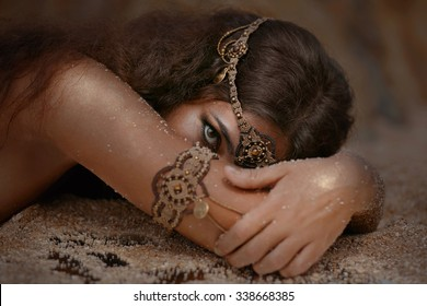 fashion model in ethnic jewelry with the mirror covered with sand