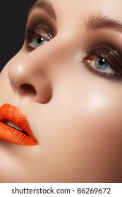 Fashion model face with bright glamour makeup. Perfect skin, wet gloss eyeshadows on eyes and vibrance orange lipstick