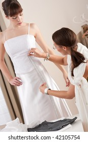 Fashion model fitting white wedding dress in professional fashion designer studio