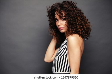 Fashion Model girl with afro curls hairstyle isolated over gray background. Beauty stylish brunette woman posing in fashionable clothes in studio. High fashion urban style