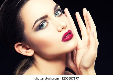 Fashion model girl beauty face close-up. Bright red lips makeup, perfect fresh clean skin. smokey eye shadows. Hand near face. Skincare facial treatment concept. Black background