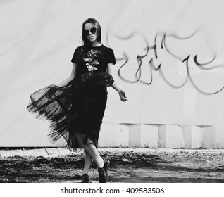 Fashion model girl in fashionable clothes. in black dress. Fashionable woman near the wall with graffiti.