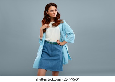 Fashion Model Girl In Fashionable Clothes On Grey Background. Beautiful Sexy Woman Wearing Stylish Clothing, White Shirt, Jeans Skirt, Light Blue Coat Jacket Posing In Studio. High Resolution