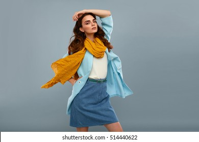 Fashion Model Girl In Fashionable Clothes On Grey Background. Beautiful Sexy Woman Wearing Stylish Clothing, White Shirt, Jeans Skirt, Light Blue Coat Jacket, Yellow Scarf In Studio. High Resolution