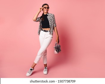 Fashion Model girl full length portrait isolated on pink background. Beauty stylish brunette woman posing in fashionable clothes in studio. Casual style, beauty accessories. High fashion urban style