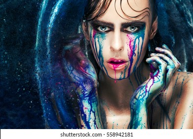 Fashion model girl portrait with colorful paint make up. Sexy woman bright color makeup. Closeup of vogue style lady face, Art design. Blue background