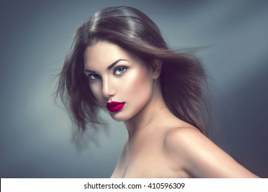 Fashion Model Girl Portrait with Long Blowing Hair. Sexy Glamour Beautiful Woman with Healthy and Beauty Brown Hair over grey background. Flying long hair
