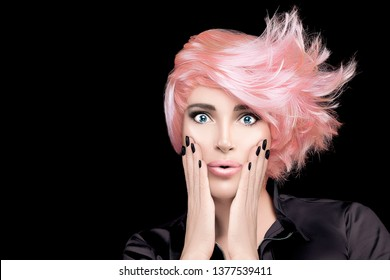 Una modelo chica con elegante pelo dorado rosa, las manos en las mejillas y la expresión guau mirando la cámara. Hermoso retrato estilo caracol aislado en negro con espacio para copiar. Concepto de peluquería en salón de belleza