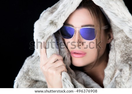 7c98a94b94 Fashion model girl wearing trend sunglasses and winter fur hood looking to  the side with a