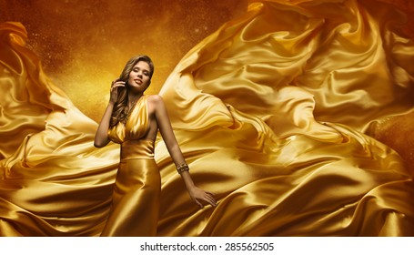 Fashion Model in Gold Dress, Beauty Woman Posing over Flying Waving Cloth, Girl with Yellow Dynamic Silk Fabric