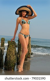 Fashion model in the hat and blue bikini bathing suit