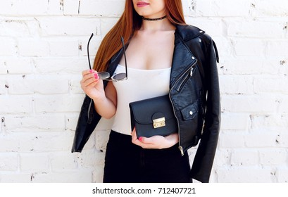 Fashion model hold stylish sunglasses wear black leather jacket outfit. Street look for spring or fall season. Punk, rock style