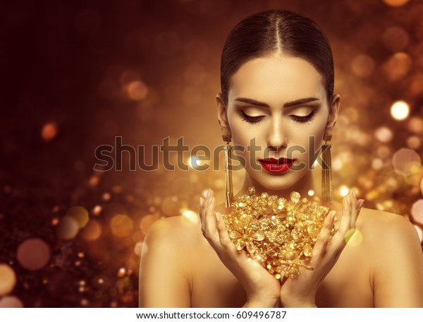 Fashion Model Holding Gold Jewelry in Hands, Woman Golden Beauty, Beautiful Girl Makeup and Luxury Jewellery