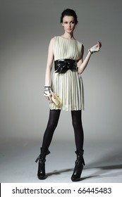 fashion model model holding little purse on gray background