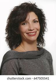 Fashion model in fashion jeans dress, beauty brunette woman posing over grey background