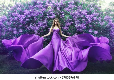 Fashion Model in Lilac Flowers, Young Woman in Beautiful Long Dress Waving on Wind, Outdoor Beauty Portrait in Blooming Garden