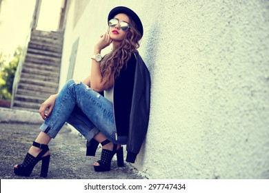 fashion model with long curly hair wearing sunglasses sitting and posing outdoor. Jeans, shoes, hat, jacket.