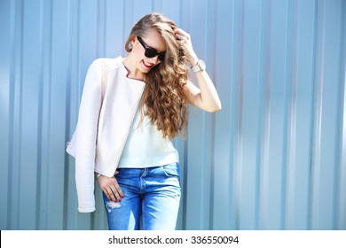 fashion model with long curly hair wearing sunglasses posing outdoor. Jeans, leather jacket.