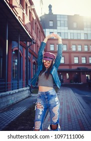 Fashion model with long hair wearing sunglasses posing outdoor. Jeans, hat, jacket.