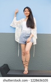 fashion model with long hair wearing short jean pants posing outdoor in front of decorated wall