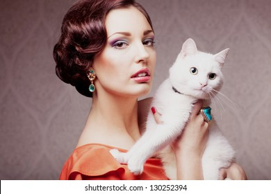 fashion model  with make up hair style and jewelry holding white cat, vintage style