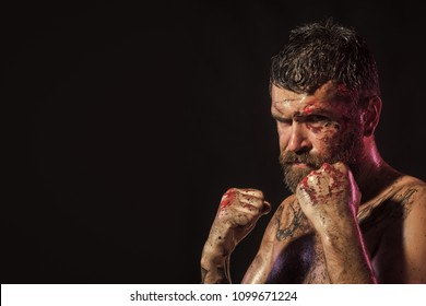 Fashion model Man fece close up. Face Man wiht happy emotion. Man in fight position with blood paint on face, fists. Bearded hipster with tattoo on chest skin on black background. Power, might, magic