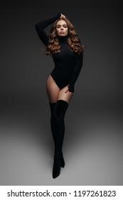 Fashion model on a gray background, fashion portrait, model in a black body