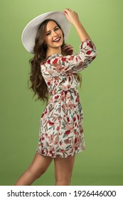 Fashion model on green background looking in camera with grat smile. she wear summer dress and a white hat. spring concept