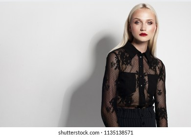 fashion model portrait. beautiful young woman with blond hair and red lips shooted on grey background