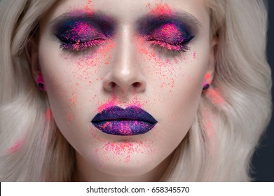Fashion model portrait with colorful powder make up and closed eyes. Beauty studio close up portrait of a blonde girl with bright color makeup. Abstract colourful make-up, Art design. Black background