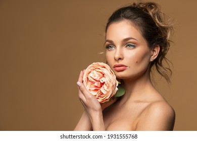 fashion model portrait o beige backround, the sweet beauty girl is keeping a pink rose flower and looking away from camera. beauty spring concept