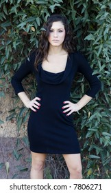 Fashion model posing in black dress in rustic serene location