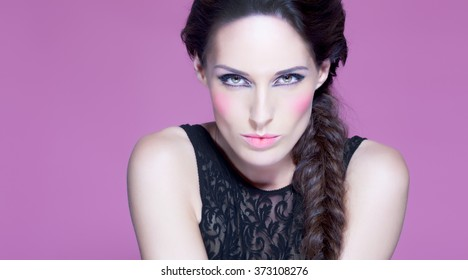 Fashion model posing over pink purple background with intense makeup. Fashion and beauty concept.