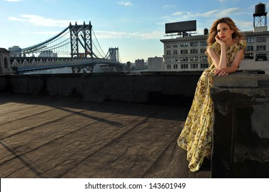 Fashion model posing sexy, wearing long evening dress on rooftop location with metal bridge construction on background