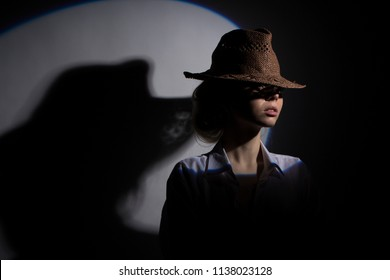 Fashion model posing at studio in hat. Beauty, fashion. Business style. Shadow play, directional light