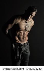 Fashion model put leather belt on jeans. Bearded man shirtless with fit torso. Man with tattoo design on skin. Sportsman with tattooed arm and chest. Bodycare with fitness and sport, vintage filter.