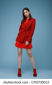 Fashion model in red suit, beautiful young woman. Studio shot. Blue background.