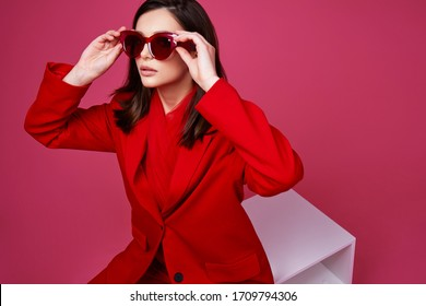 Fashion model in red suit and sunglasses. Studio shot.