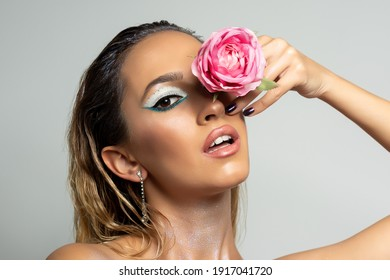 Fashion model with rose flower on bright background. Beautiful young woman portrait.