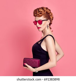 Fashion Model in Sexy Jumpsuit. Stylish Mohawk hairstyle, Sunglasses, Summer Party Disco Outfit. Beauty Redhead Woman in Trendy Luxury Accessories. Glamour fashionable Lady. Playful Girl on Pink.