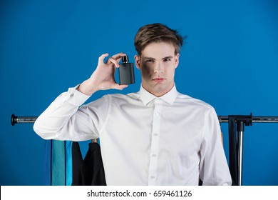 fashion model with shaved face in white shirt, hold perfume bottle on blue background