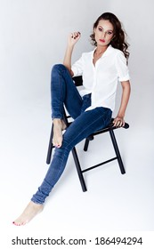 Fashion model sitting on a chair in a blouse and jeans barefoot on a white background