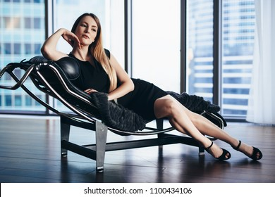 Fashion model with slim long legs wearing black cocktail dress lying on lounge chair in penthouse apartment