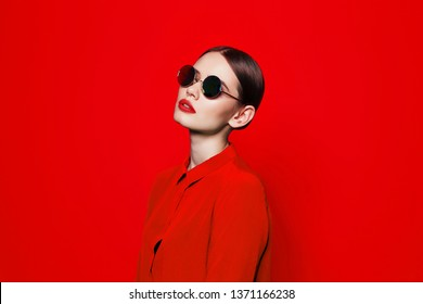 fashion model in sunglasses, beautiful young woman. Red blouse, Red background