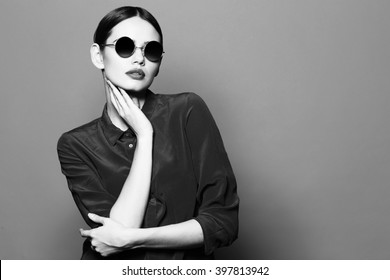 fashion model in sunglasses , beautiful young woman. Black and white studio shot