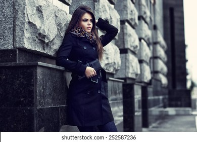 Fashion model with sunglasses, black coat, scarf, and handbag clutch. Outdoor shot