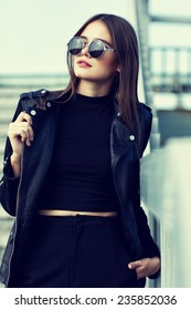 fashion model in sunglasses and black leather jacket posing outdoor