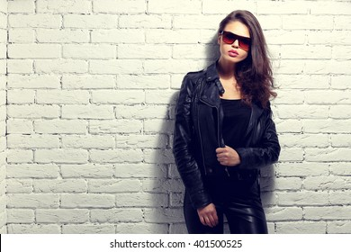 fashion model in sunglasses, black leather jacket, leather pants. Posing near white brick wall.