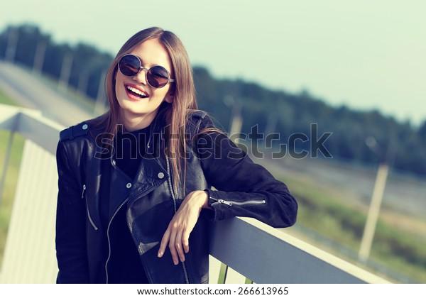 サングラスと屋外でポーズを取る黒い革のジャケットのファッションモデル