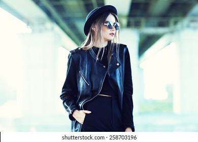 fashion model in sunglasses, hat and black leather jacket posing outdoor.